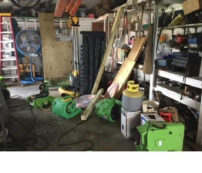 Our equipment sitting inside a garage drying water damage after a heater started leaking