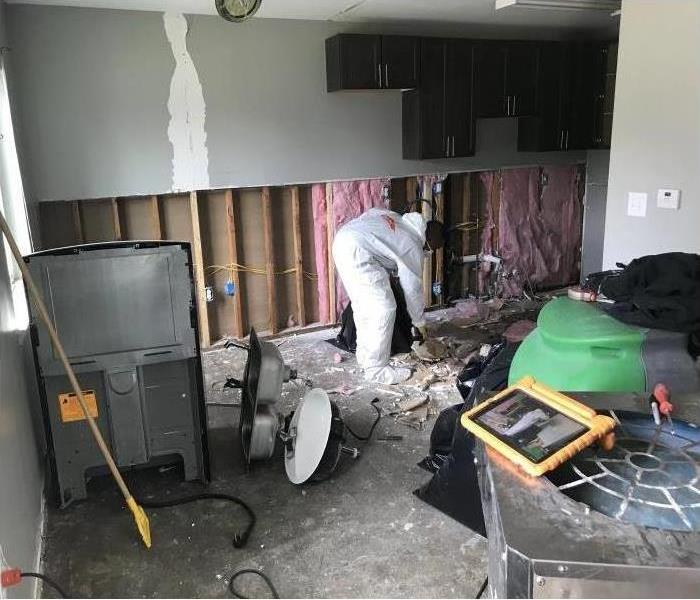 One of our technicians working on restoring the walls in a home after water and mold damaged them